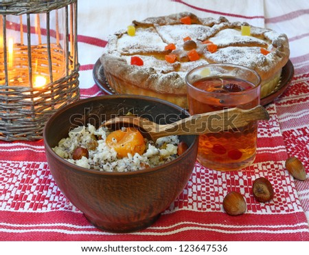 Ukrainian Christmas meal kutya of wheat grain, poppy seed, honey, nuts and raisins in an antique bowl on a embroidery - stock photo