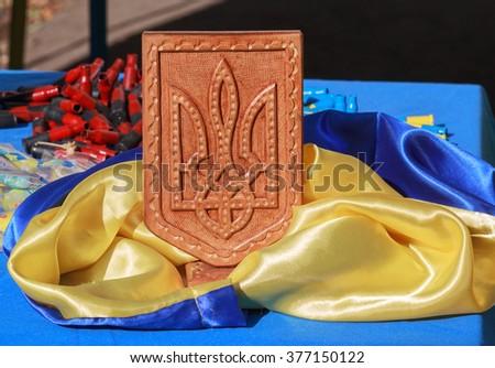 Ukrainian flag, coat of arms and machine-gun shells painted in patriotic colors - stock photo