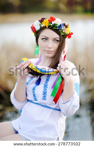 Ukrainian girl in a shirt and a flower wreath on his head on a background of the river - stock photo