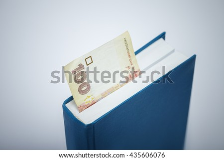 Ukrainian money bookmark in the book. Ukrainian education corruption concept. Low aperture shot, focus on number and part of the book. - stock photo