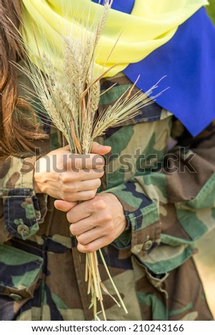 Ukrainian patriot with a wheat in a hands and ukrainian flag scarf on shoulders