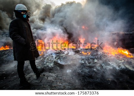 Ukrainian revolutionary standing near the fire in the street Hrushevskoho. Ukraine, Kiev on January 23, 2014.