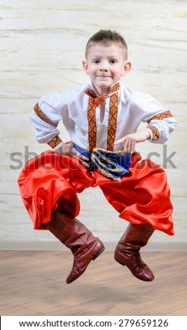 Ukrainian talented child performing a traditional dance move with a leap in mid air while wearing folk costume during a cultural artistic representation - stock photo
