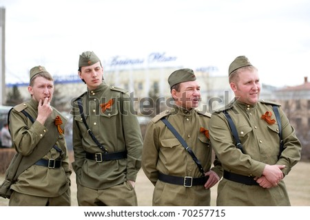 ULAN-UDE, RUSSIA - MAY 9: A group of actors wearing vintage (WWII's period) uniforms watch their colleagues perform on annual Victory Day, May, 9, 2009 in Ulan-Ude, Buryatia, Russia. - stock photo