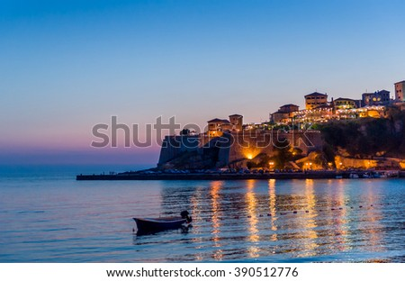 Ulcinj old town fortress with purple after sunset light. Adriatic sea, small fishing boat and fortress walls at night, Montenegro.
