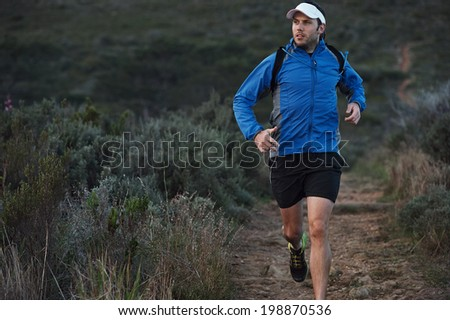 ultra marathon trail runner training in mountains for fitness and exercise wearing windbreaker - stock photo