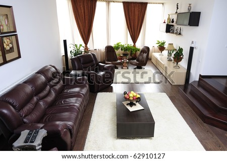 Ultra-modern living-room with leather sofa and armchairs near big windows with curtains - stock photo