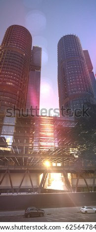 Ultra modern twin towers with afternoon sun shining through office bridge