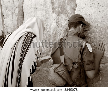 Ultra-orthodox and soldier, that are prayed in western wall in Jerusalem. - stock photo