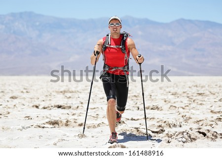 Ultra running man - trail runner in extreme race training for marathon. Fit male athlete running with trekking hiking poles in Death Valley, USA. - stock photo
