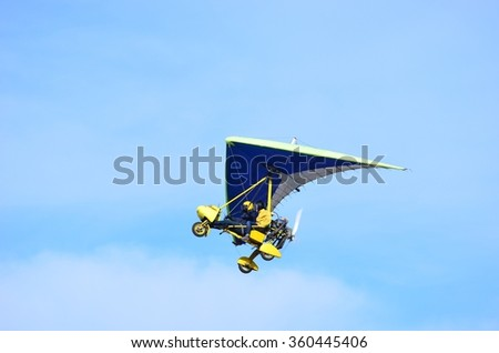 Ultralight trike flying with a pilot and a passenger against mountains