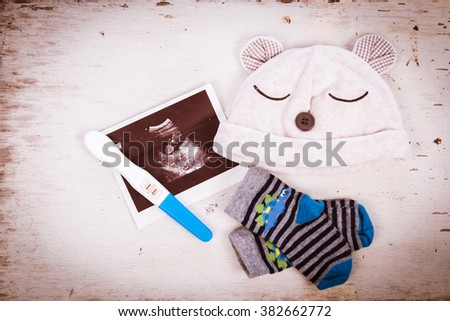 ultrasound with pregnancy test on wooden background - stock photo