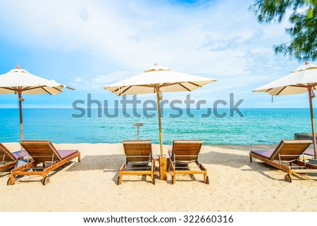 Umbrella and beach chair with beautiful tropical beach - summer vacation background