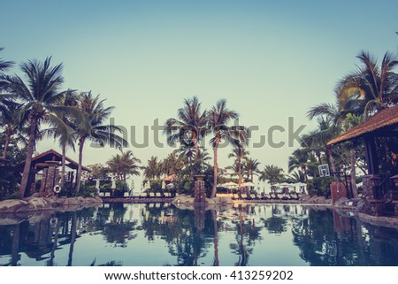 Umbrella and chair around luxury swimming pool landscape with palm tree in hotel resort - Vintage Filter and Boost up color Processing - stock photo