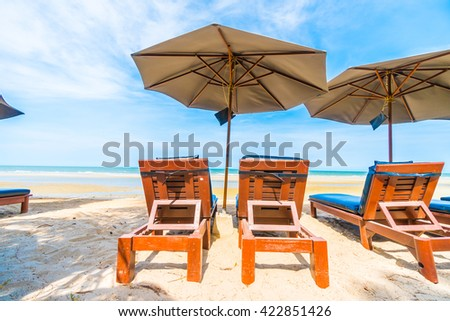 Umbrella and chair on the beautiful tropical beach and sea with coconut palm tree - Boost up color processing