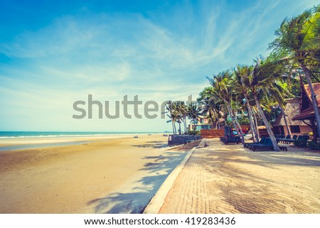 Umbrella and chair on the beautiful tropical beach and sea with coconut palm tree - Vintage Filter