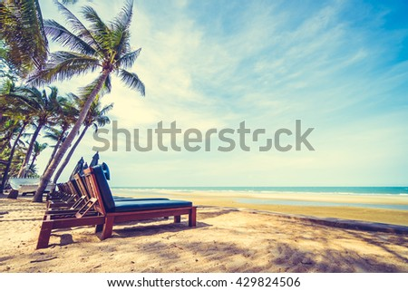 Umbrella and chair on the beautiful tropical beach and sea with coconut palm tree - Vintage Filter - stock photo