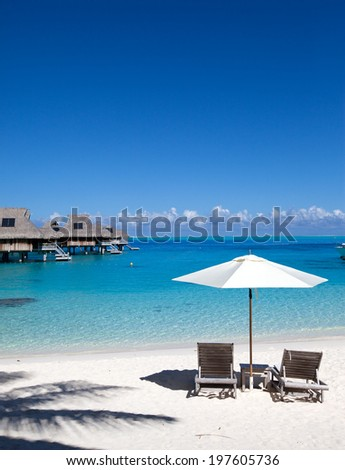 Umbrella and chaise lounges on a beach. - stock photo