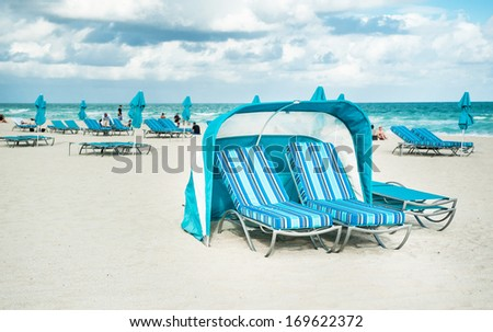 Umbrella and lounge chairs along  of Miami Beach. - stock photo