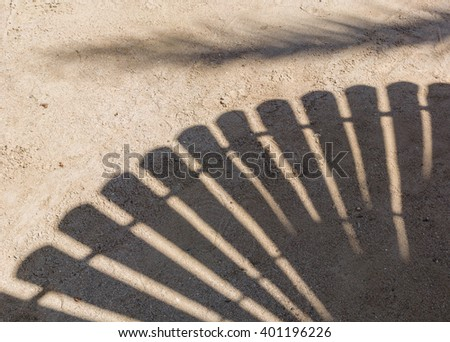 umbrella cast shadows on the smooth golden sand of a remote tropical island beach - stock photo