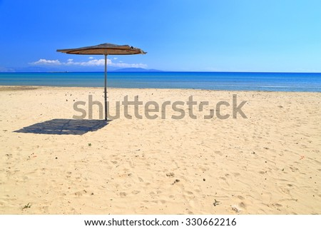 Umbrella isolated on golden beach by the Aegean sea, Greece - stock photo