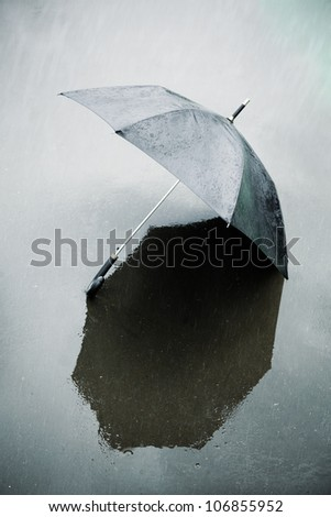 umbrella on the wet asphalt - stock photo