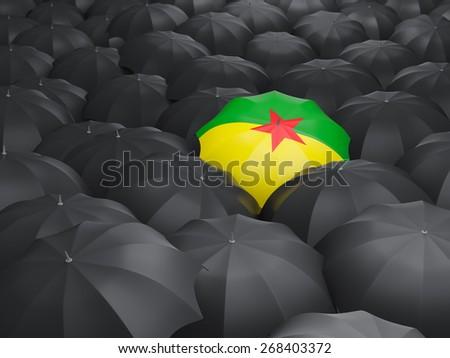 Umbrella with flag of french guiana over black umbrellas - stock photo