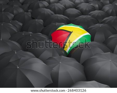 Umbrella with flag of guyana over black umbrellas - stock photo