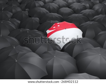 Umbrella with flag of singapore over black umbrellas - stock photo