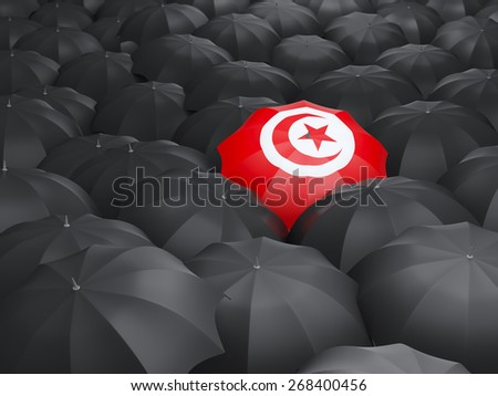 Umbrella with flag of tunisia over black umbrellas - stock photo