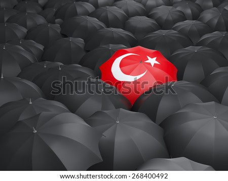 Umbrella with flag of turkey over black umbrellas - stock photo