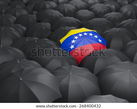 Umbrella with flag of venezuela over black umbrellas - stock photo