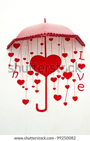 umbrella with heart drops painting on wall - stock photo