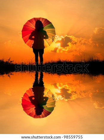 Umbrella woman and sunset silhouette,Water reflection