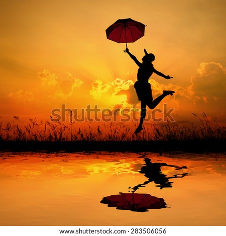 Umbrella woman and sunset silhouette,Water reflection.copy space - stock photo