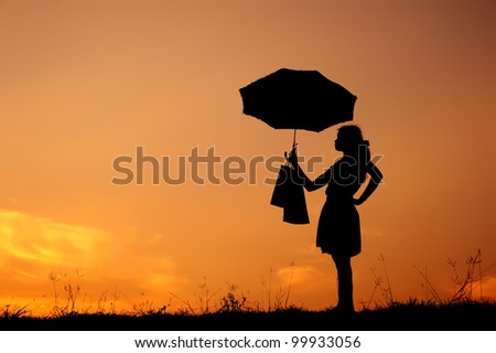 Umbrella Woman holding shopping bags  in sunset silhouette