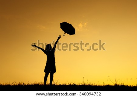 Umbrella woman stand and sunset silhouette with copy space. - stock photo