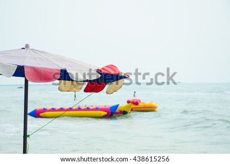 Umbrellas and Colorful banana boat on the beach With Copy space for captions.Beach umbrella on a sunny day sea in background