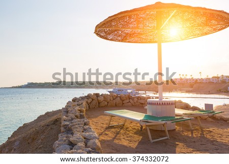 Umbrellas and empty deckchairs on the beach during sunset - stock photo