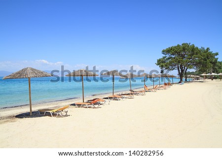 Umbrellas and recliners by the sea on exotic resort, Thassos island - Greece