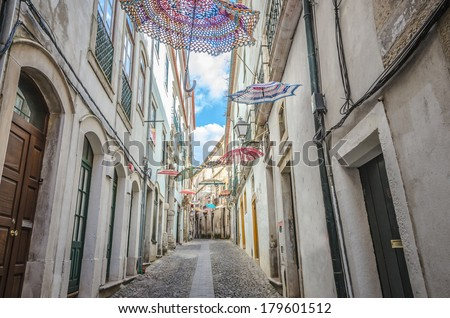 Umbrellas decorating the streets of Coimbra, Portugal, on a cloudy day - stock photo