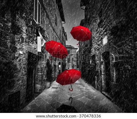 Umbrellas flying with wind and rain on dark narrow street in an old Italian town in Tuscany, Italy.. Black and white with red - stock photo
