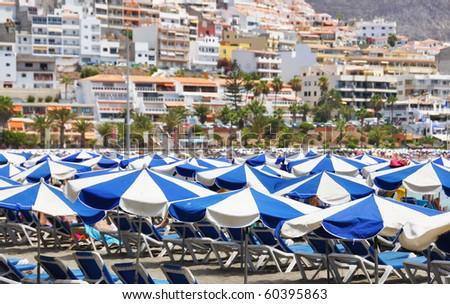 Umbrellas on the beach of Playa de las Americas. Tenerife, Canaries - stock photo