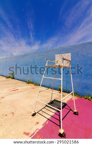 Umpire chair in the old tennis court with blue sky background. - stock photo