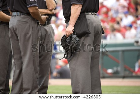 umpire crew meets before the game at home plate - stock photo