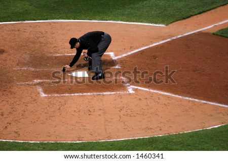 Umpire dusting off home plate - stock photo