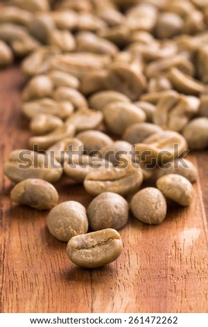Un-roasted green coffee beans placed on a wooden cutting board. - stock photo