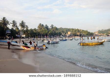 UNAWATUNA, SRI LANKA - JANUARY 17: Tamil men doing a traditional fishing on a beach January 17, 2014 in Arugan Bay ,Sri Lanka. This activity will provide a income stream for people. - stock photo