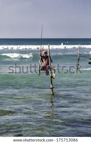 UNAWATUNA, SRI LANKA - JANUARY 25, 2014: Unidentified stilt fishermen at Unawatuna, Sri Lanka. Stilt fishing is special to Galle district and thereare about 500 fishing families in the coastal belt. - stock photo