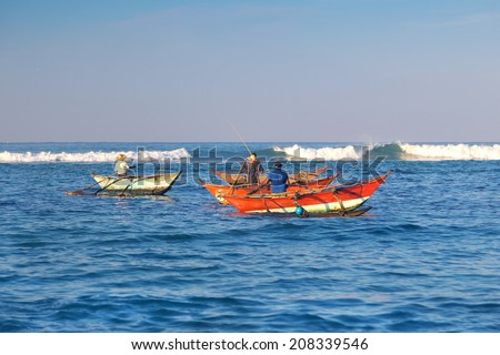 UNAWATUNA, SRI LANKA - MARCH 6, 2014: Fishermen in their traditional boats catching fish. Tourism and fishing are two main business in this town.